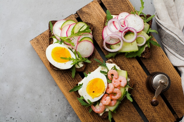 오래 된 어두운 표면에 계란, 새우, 무, 오이, 크림 치즈 및 arugula와 함께 어두운 호밀 빵에 오픈 샌드위치. smorrebrod 덴마크 요리의 전통 요리. 평면도.