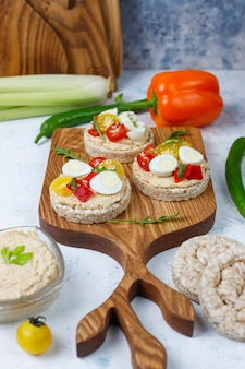 Open sandwiches of rice cakes with hummus , vegetables and quail egg, healthy breakfast or lunch