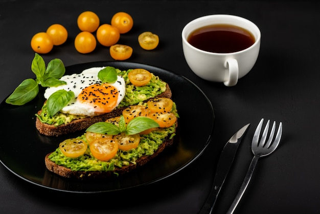 Open sandwiches with avocado guacamole, yellow cherry tomatoes, fried egg and basil on a black plate . healthy food or snack