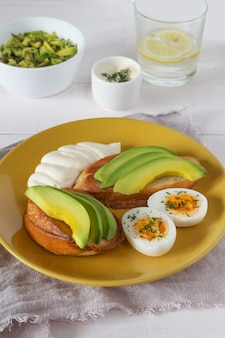 Open sandwiches with avocado on yellow plate