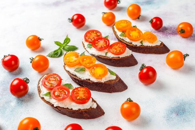 Открытые бутерброды с творогом, помидорами черри и базиликом.