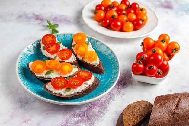 カッテージ チーズ、チェリー トマト、バジルのオープン サンドイッチ。