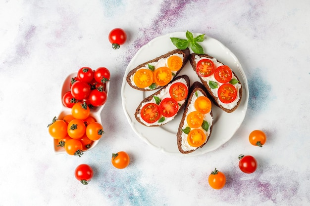 Open sandwiches with cottage cheese,cherry tomatoes and basil. Free Photo