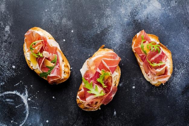 Открытые бутерброды с хамоном, рукколой и твердым сыром на бетонной старой темной поверхности
