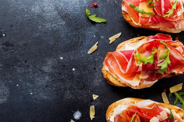 コンクリートの上にハモン、ルッコラ、ハード チーズを乗せたオープン サンドイッチ