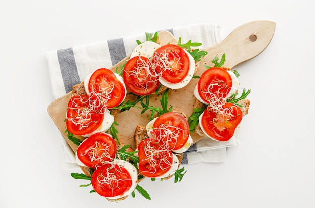 Open sandwiches with mozzarella cheese, tomatoes and arugula on white backgrounbd. top view, italian cuisine