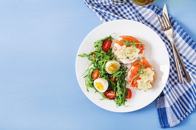 Open sandwiches with salmon, cream cheese and rye bread in a white plate and salad