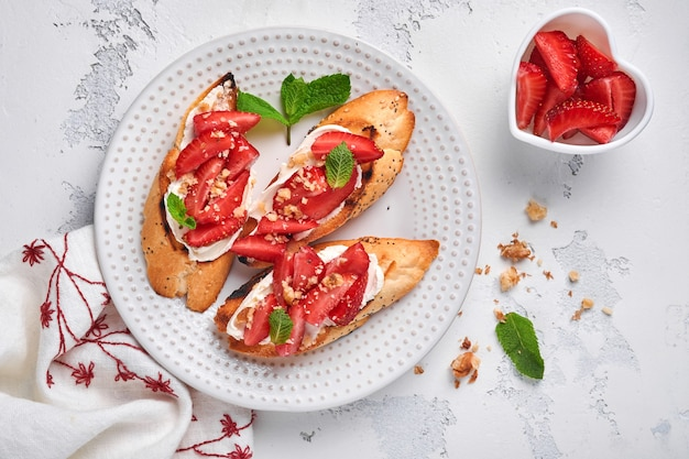 밝은 회색 돌 배경에 세라믹 접시에 딸기, 부드러운 치즈 민트, 호두를 넣은 오픈 샌드위치. 여름과 건강한 다이어트 음식, 채식주의 음식 개념. 평면도.