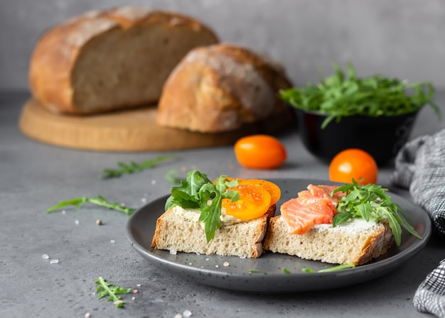 Open sandwiches with wheat and rye bread, tomatoes, smoked salmon and arugula