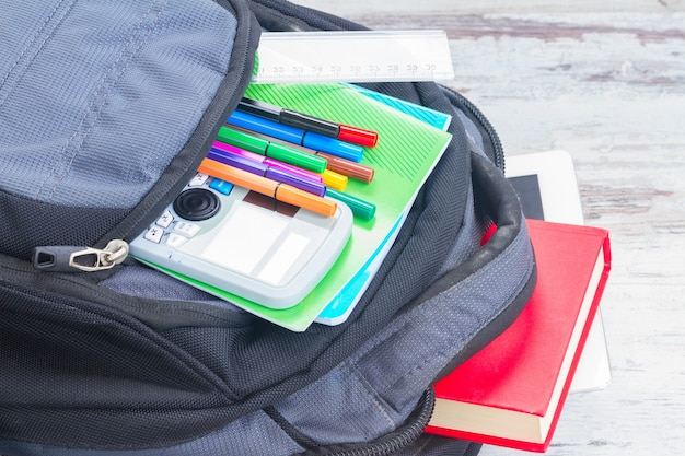 Open school backpack with supplies close up