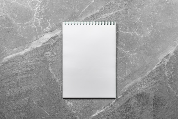 Open school notebook on marble table top view, notepad with blank page. flat lay of office concept