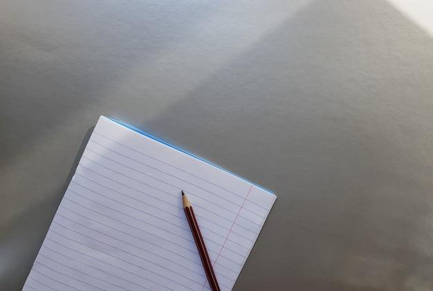 Откройте школьную тетрадь с ручкой на сером столе с солнечными лучами из окна. чистый белый лист тетради для записи. концепция образования. скопируйте пространство. вид сверху. плоская планировка.