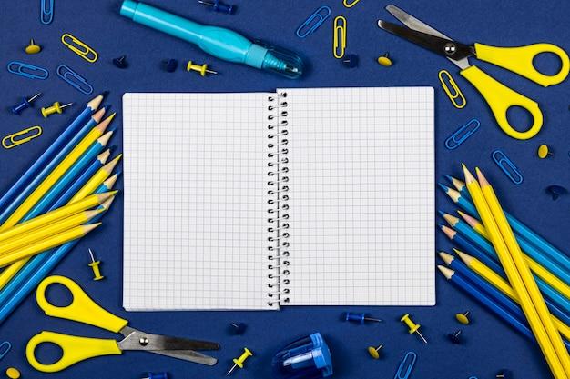 Откройте школьную тетрадь с местом для текста и канцелярских принадлежностей желтого и синего цвета на синем фоне.