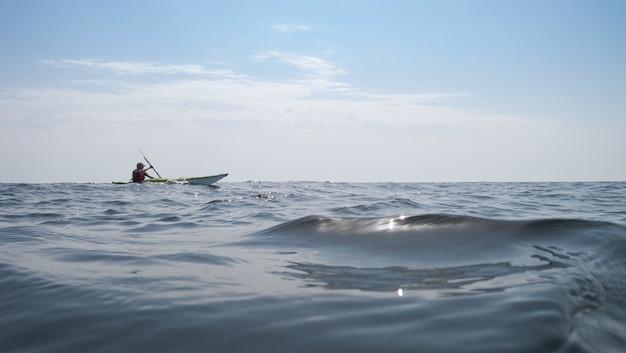 Открытое море. мужчина плывет на байдарке на заднем плане