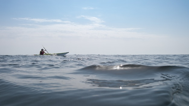 Open sea. a man is sailing on a kayak in the background
