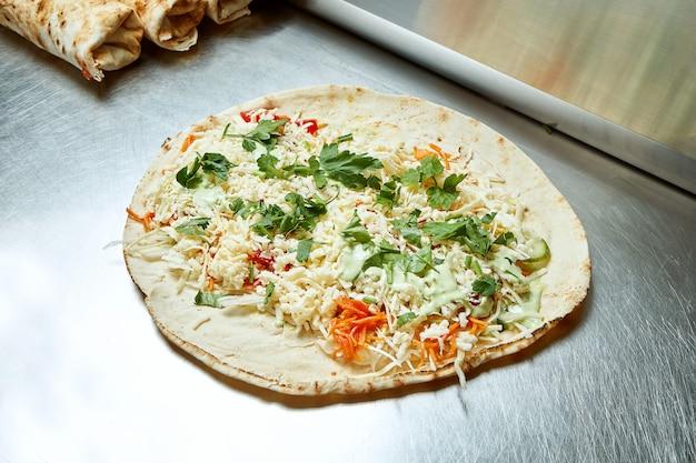Раскройте шаурму с сыром, овощами, капустой, зеленью и белым лавашом на металлической поверхности. вкусный уличный шашлык