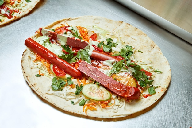 Open shawarma with smoked sausage vegetables, cabbage, herbs and white pita sauce on a metal surface. tasty street food kebab Premium Photo