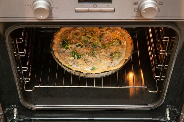 오븐에서 구운 닭고기와 브로콜리를 곁들인 쇼트브레드 파이에 치즈를 뿌린 후