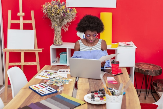 어깨를 벌리십시오. 사무실에서 일하는 열린 어깨와 셔츠를 입고 아프리카 계 미국인 디자이너