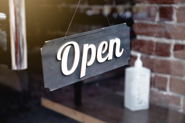 Open sign hanging front of cafe and sanitizer bottle cafe entrance during covid-19 pandemic