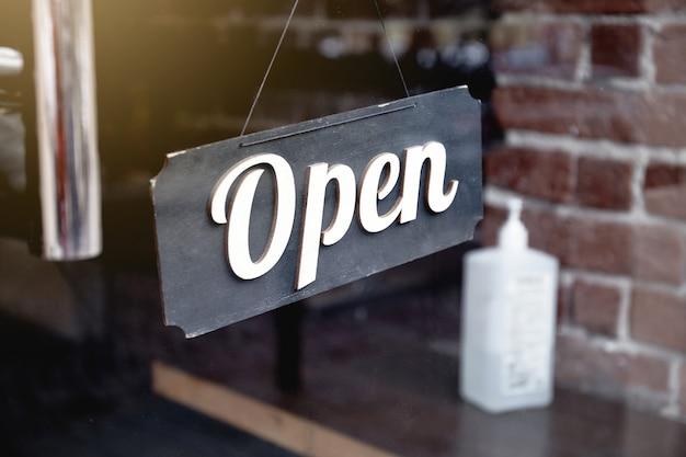 Covid-19 대유행 기간 동안 카페 및 소독제 병 카페 입구 전면에 매달려있는 오픈 사인