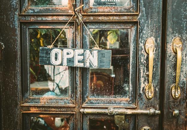 ヴィンテージのドアにぶら下がっているオープンサイン