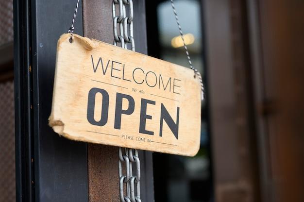 コーヒーショップのドアにサインを開き、ビジネスはcovid-19発生の概念の後に再開します。