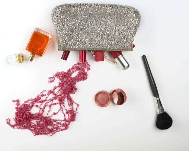 Open silver cosmetic bag and women's cosmetics and perfumes, red lipstick
