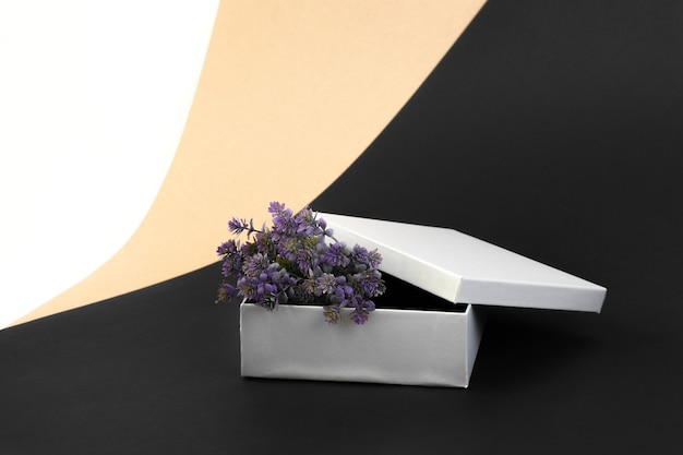 Open silver gift box with purple artificial flowers