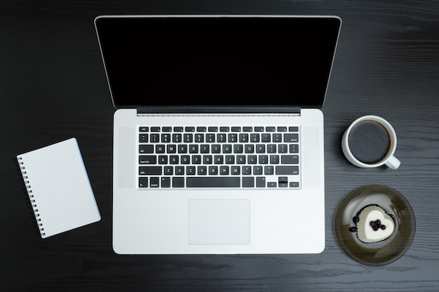 Открытый серебряный ноутбук, кружка кофе, блокнот и десерт на черном фоне