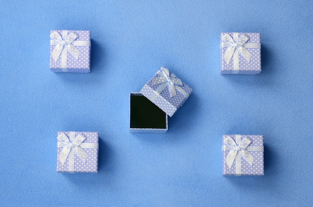 Open small gift box in blue with a small bow lies on a blanket of soft and furry light blue fleece fabric.