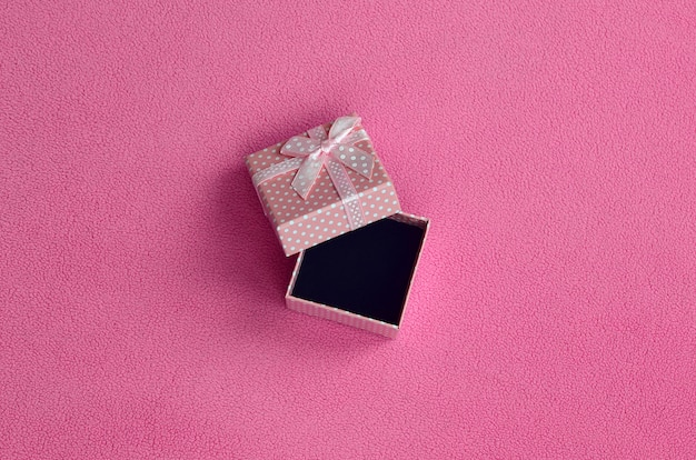 Open small gift box in pink with a small bow lies on a blanket of soft and furry light pink fleece fabric.