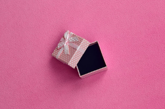 Open small gift box in pink with a small bow lies on a blanket
