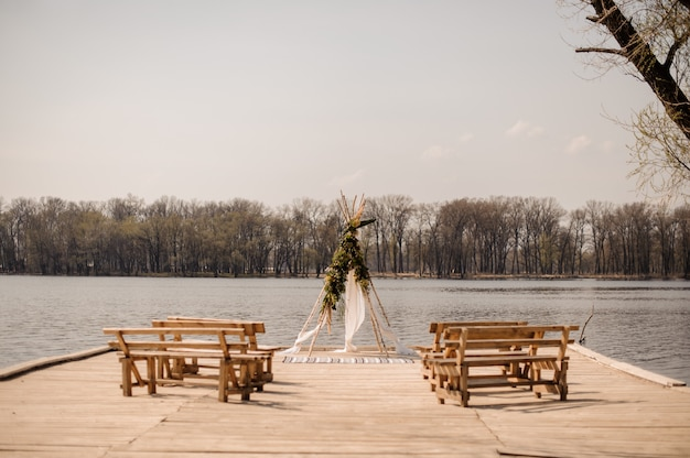 Open space for european wedding ceremony with wooden benches and handmade arch decorated with tropical flowers