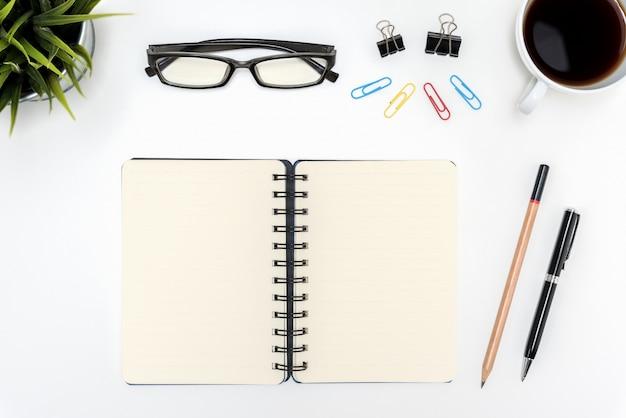 白い机のテーブル上に開いたスパイラルの空白のノートブック