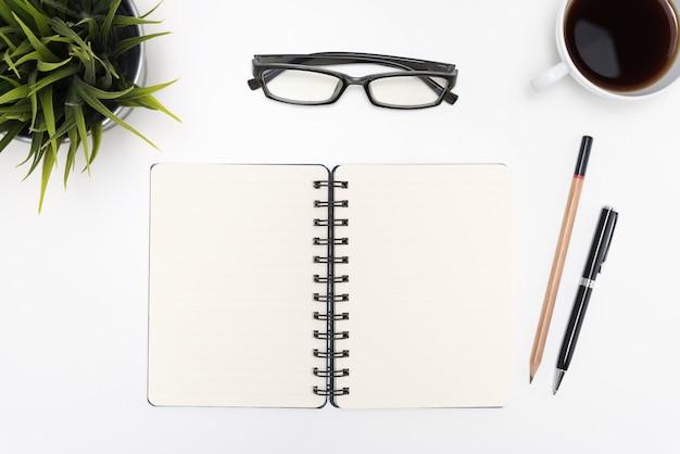 白い机の上に開いたスパイラルの空白のノートブック