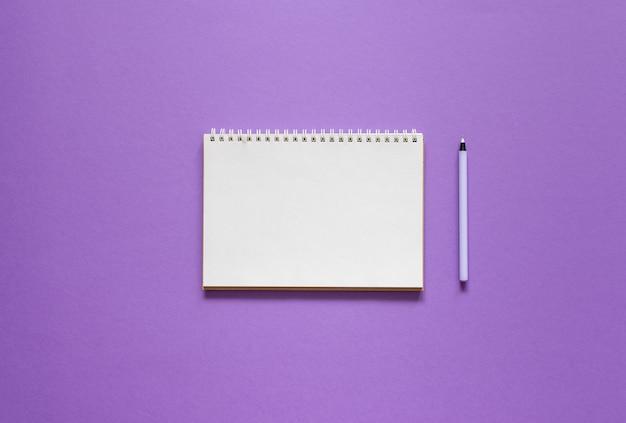 紫色の背景にスパイラルメモ帳を開く、ノートブックとペンはテクスチャ紙に横たわる、フラットレイコンセプト
