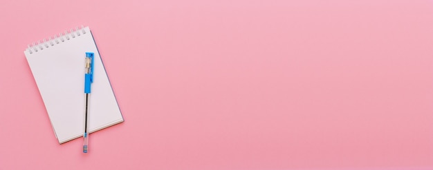 Открытый спиральный блокнот на розовом фоне блокнота и синяя ручка лежат на бумажной плоской планировке