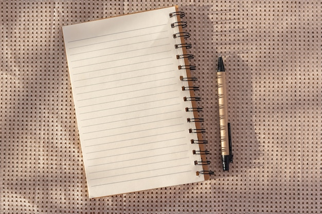 Open spiral notepad and pen on a table background. fashion shadow concept. sunlight. desktop, copy space.