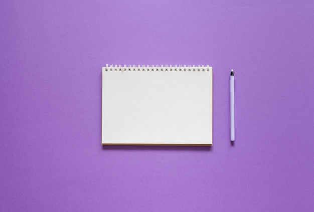 Open spiral notepad on a purple background , notebook and pen lie on textural paper, flat lay concept