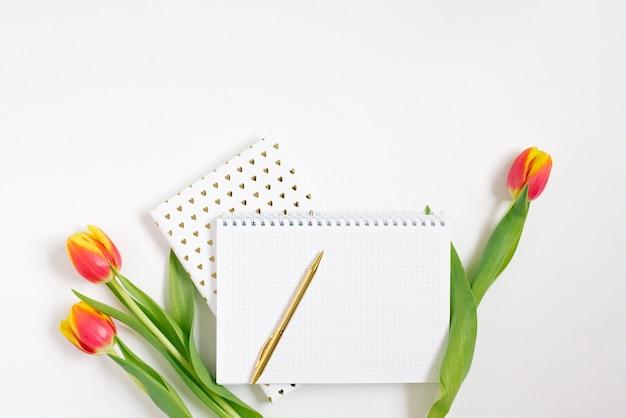 白い机の背景にペンと赤いチューリップでスパイラルメモ帳を開きます。