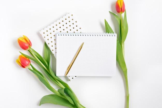 흰색 책상 배경에 펜과 빨간 튤립이 있는 열린 나선형 메모장