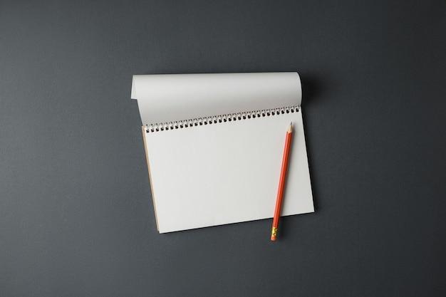 Открытый спиральный блокнот с белыми страницами и карандашом на серой стене горизонтальной фотографии вид сверху.