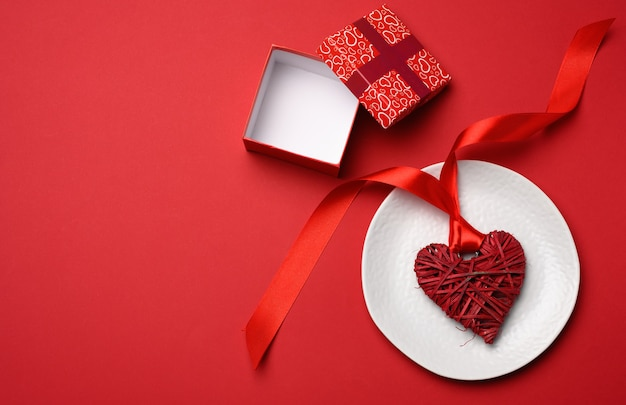 Open square cardboard box and wicker heart with silk ribbon in white ceramic plate, top view