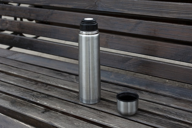 Открытый стальной металлический термос с чаем или кофе на деревянной скамейке.