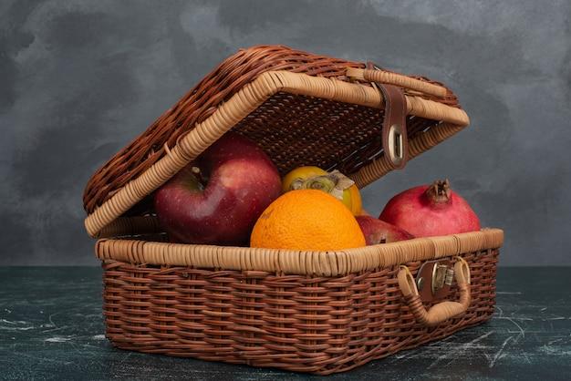Apra la valigia piena di frutti sulla superficie in marmo.
