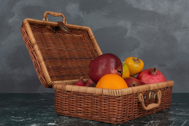 Apra la valigia piena di frutta sulla parete di marmo.