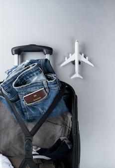 Open suitcase packed for travelling with thailand passport on grey background