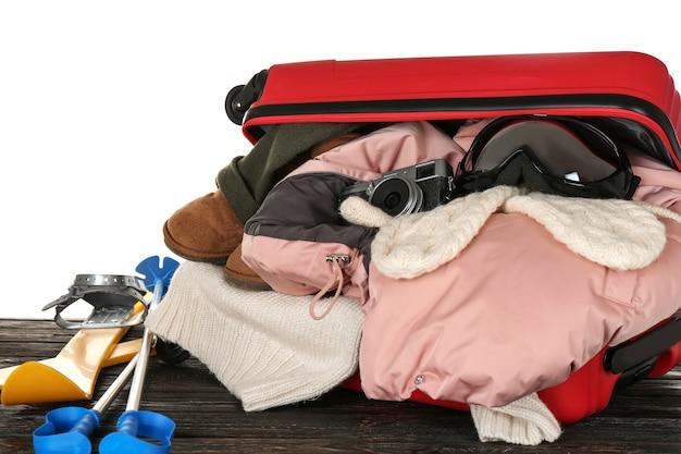 Открытый чемодан с теплой одеждой и лыжным снаряжением на деревянном столе против белого. концепция зимнего отдыха