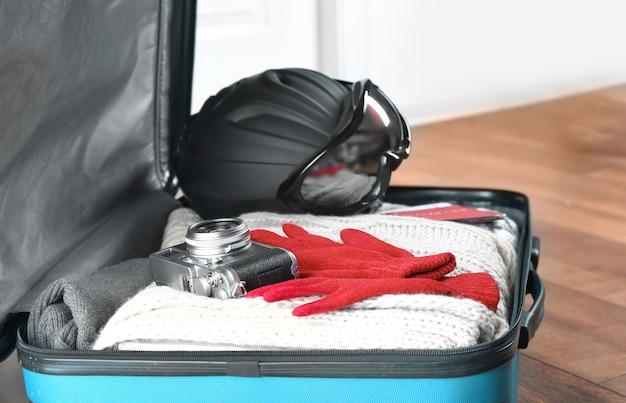 Открытый чемодан с теплой одеждой, фотоаппаратом и лыжным снаряжением на полу. концепция зимнего отдыха